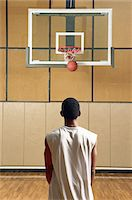 Young male basketball player making a basket, rear view Stock Photo - Premium Royalty-Freenull, Code: 6106-05564000