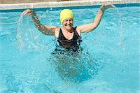 seniors and swim cap - Senior woman splashing in swimming pool, arms raised, laughing Stock Photo - Premium Royalty-Freenull, Code: 6106-05565842