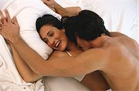 Romantic couple embracing on bed, elevated view Stock Photo - Premium Royalty-Freenull, Code: 6106-05567337