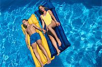 Teenage boy and girl floating in pool Stock Photo - Premium Royalty-Freenull, Code: 6106-05568164