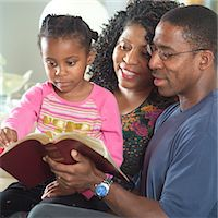 Mother and father reading Bible with daughter (5-7) Stock Photo - Premium Royalty-Freenull, Code: 6106-05570205