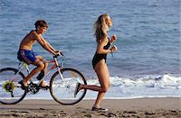 Teenage boy (14-15) riding bike and teenage girl (16-17) jogging on beach, side view Stock Photo - Premium Royalty-Freenull, Code: 6106-05570721