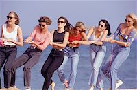 Group of women playing tug-of-war on beach Stock Photo - Premium Royalty-Freenull, Code: 6106-05573063
