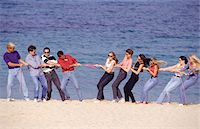 Group of people playing tug-of-war on beach, women against men Stock Photo - Premium Royalty-Freenull, Code: 6106-05573070