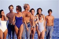 Medium group of young people walking on beach, front view Stock Photo - Premium Royalty-Freenull, Code: 6106-05575655