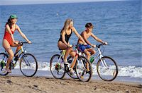 Mother with daughter (16-17) and son (12-13) riding bikes on beach Stock Photo - Premium Royalty-Freenull, Code: 6106-05576376