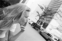 Young woman smoking cigarette in street, side view, (B&W) Stock Photo - P
