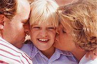 Parents kissing daughter (8-9), close-up Stock Photo - Premium Royalty-Freenull, Code: 6106-05576736