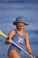 Girl wearing sun hat, standing holding paddles, looking down, smiling Stock Photo - Premium Royalty-Freenull, Code: 6106-05579148