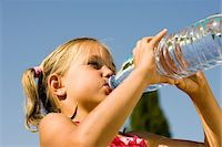 Girl (5-7) drinking from water bottle in garden, low angle view Stock Photo - Premium Royalty-Freenull, Code: 6106-05581748