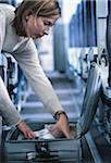 Woman searching in suitcase, in airplane Stock Photo - Premium Royalty-Freenull, Code: 6106-05582344