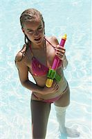 Woman holding water pistol in swimming pool Stock Photo - Premium Royalty-Freenull, Code: 6106-05582631