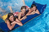 Girls lying on pool raft in swimming pool Stock Photo - Premium Royalty-Freenull, Code: 6106-05583327