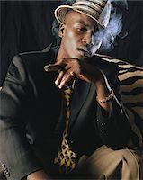 Man sitting smoking cigar, portrait Stock Photo - Premium Royalty-Freenull, Code: 6106-05583691