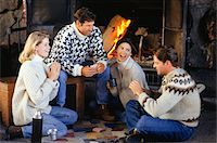 sweater and fireplace - Two couples sitting by fireplace, playing card game Stock Photo - Premium Royalty-Freenull, Code: 6106-05583976