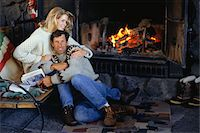 sweater and fireplace - Couple sitting in ski lodge by fireplace, embracing Stock Photo - Premium Royalty-Freenull, Code: 6106-05584009