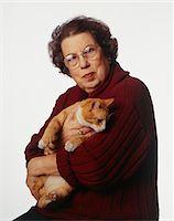 Senior woman holding cat, posing in studio, portrait Stock Photo - Premium Royalty-Freenull, Code: 6106-05584229
