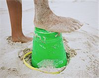 Girl (10-12) with sandy foot on plastic bucket at beach, low section Stock Photo - Premium Royalty-Freenull, Code: 6106-05585394