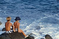 Girl (6-9) and boy (10-13 months) sitting at sea side Stock