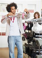 Woman watching man hold up g-strings on hangers in shop Stock Photo - Premium Royalty-Freenull, Code: 6106-05586251