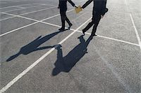 person walking on parking lot - Criminal Businessman Passing a Folder to Another Businessman in a Carpark Stock Photo - Premium Royalty-Freenull, Code: 6106-05587430