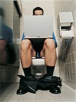 Half Dressed Businessman Using a Laptop Sitting in a Lavatory Stock Photo - Premium Royalty-Freenull, Code: 6106-05587628