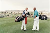 Rear View Portrait of Two Senior Men Standing on a Putting Green Carrying Golf Bags Stock Photo - Premium Royalty-Freenull, Code: 6106-05588117