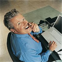 Portrait of a Ceo Smoking a Cigar at His Desk Stock Photo - Premium Royalty-Freenull, Code: 6106-05588484