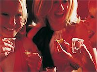 Three Smiling, Young Women Having Tequila and Slices of Lime at a Bar Stock Photo - Premium Royalty-Freenull, Code: 6106-05589677
