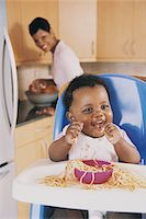 Portrait of a Baby in a High Chair Eating Spaghetti and Mum in the Background Stock Photo - Premium Royalty-Freenull, Code: 6106-05589687