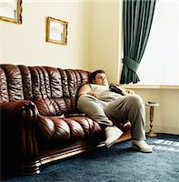 fat man full body - Young Man Lying on a Sofa Watching TV and Holding a Packet of Crisps Stock Photo - Premium Royalty-Freenull, Code: 6106-05589970