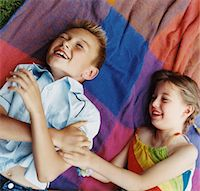Girl Tickling Her Brother on Blanket Stock Photo - Premium Royalty-Freenull, Code: 6106-05590302