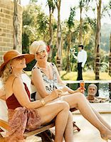 Two Elegant Senior Women in Swimsuits Sit By a Pool, a Senior Man in the Pool and Their Butler in the Background Stock Photo - Premium Royalty-Freenull, Code: 6106-05590856
