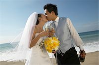 Newlywed Couple Kiss and Hold Champagne Glasses at Waters Edge on a Beach Stock Photo - Premium Royalty-Freenull, Code: 6106-05591424