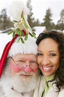 Portrait of a Woman Standing Close to Father Christmas Under the Mistletoe Stock Photo - Premium Royalty-Freenull, Code: 6106-05592313