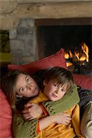 sweater and fireplace - Mother Cuddling Her Son on a Sofa in a Living Room Stock Photo - Premium Royalty-Freenull, Code: 6106-05592466