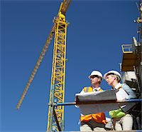 Two Well Dressed Colleagues Looking at Blueprints on a Building Site, with a Crane in the Background Stock Photo - Premium Royalty-Freenull, Code: 6106-05593481