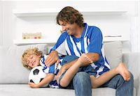 Father and Son Wearing Football Strips, Sitting on a Sofa and Playing Together Stock Photo - Premium Royalty-Freenull, Code: 6106-05594110