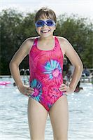lifestyle portrait of a female child in a pink swimsuit and goggles as she stands in a pool and smiles Stock Photo - Premium Royalty-Freenull, Code: 6106-05595620