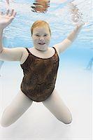 preteen girl - underwater lifestyle shot of a female child in a animal print swimsuit as she plays in a pool Stock Photo - Premium Royalty-Freenull, Code: 6106-05595625