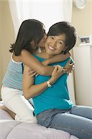 preteen kissing - lifestyle shot of a teenage girl in her bedroom as she lovingly hugs her mother Stock Photo - Premium Royalty-Freenull, Code: 6106-05595871
