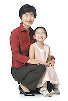 female white background full body - an attractive asian mother sits with her young daughter and smiles at the camera Stock Photo - Premium Royalty-Freenull, Code: 6106-05596140