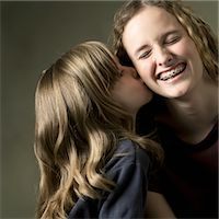 preteen kissing - studio portrait of a caucasian female child as she kisses the cheek of her big sister Stock Photo - Premium Royalty-Freenull, Code: 6106-05596307