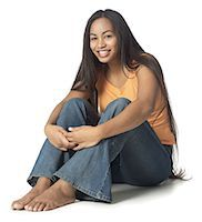 an ethnic female teenager in jeans and an orange shirt sits down and smiles brightly Stock Photo - Premium Royalty-Freenull, Code: 6106-05596437