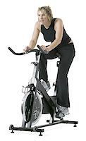 female white background full body - full length shot of an adult woman in a black workout outfit as she rides an exercise bike Stock Photo - Premium Royalty-Freenull, Code: 6106-05597128