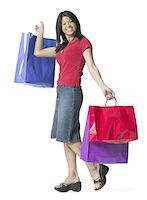 female white background full body - full length shot of a young adult woman as she playfully holds up numerous shopping bags Stock Photo - Premium Royalty-Freenull, Code: 6106-05597165