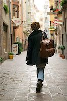 lifestyle shot of an adult female with a backpack as she strolls down a european street Stock Photo - Premium Royalty-Freenull, Code: 6106-05597400