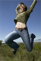 Low angle view of a young woman standing on a grassy field with her arms raised Stock Photo - Premium Royalty-Freenull, Code: 6106-05597566