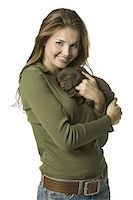 Portrait of a young woman holding a puppy Stock Photo - Premium Royalty-Freenull, Code: 6106-05597580