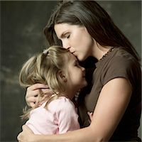 a young caucasian mother kisses the forehead of her young daughter on her lap Stock Photo - Premium Royalty-Freenull, Code: 6106-05598042